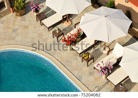 Swimming pool in small hotel yard with parasols and chaise-longues - stock photo