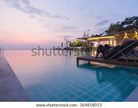 Swimming pool in the backyard with sunset scene background and people relaxing on sunbed - stock photo