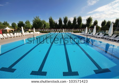 swimming pool, located in the open. A calm, clear blue water - stock photo