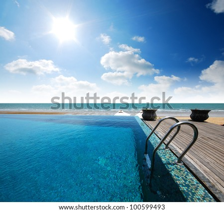 Swimming pool near the beach at high class resort in thailand for relax relaxation beautiful sea sand sun blue sky in Thailand - stock photo
