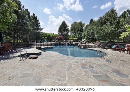 Swimming pool of luxury home with large stone patio - stock photo