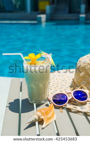 Swimming pool table with sunglasses, hat and fresh cocktail - Selective focus - stock photo