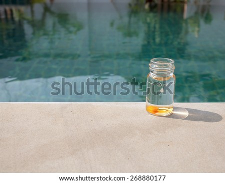 Swimming pool water testing bottle with orange tablet  with space on the swimming pool edge - stock photo