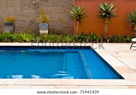 Swimming pool with blue water and palm trees - stock photo