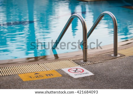 swimming pool with  ladder and warning sign - stock photo