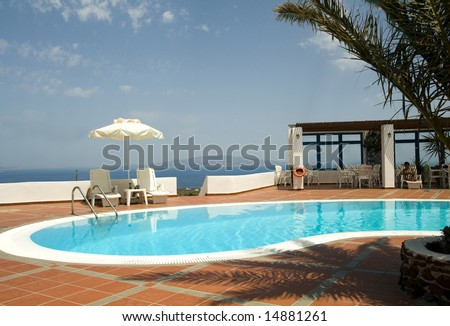 swimming pool with mediterranean sea view oia ia santorini thira greek cyclades islands greece - stock photo