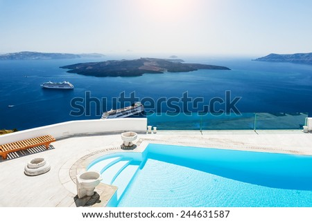 Swimming pool with sea view. White architecture on Santorini island, Greece.  Beautiful landscape with sea view - stock photo