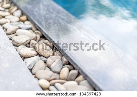 Swimming pool with shining blue water and sun glare bordered with natural pebble path framed with stone. Decoration and design of pools. Relaxation and spa. - stock photo