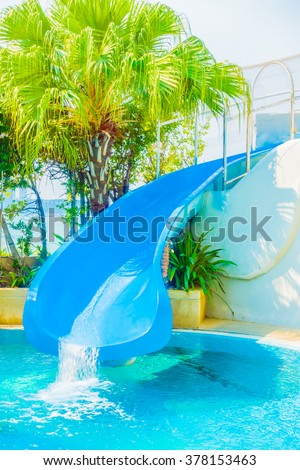 Swimming pool with slider in hotel pool resort - stock photo