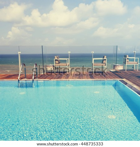 Swimming pool with sparkling shiny sun blue water. Mediterranean seascape in the background. Toned colors   - stock photo