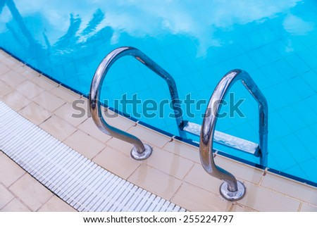 Swimming pool with stair and palm reflection at hotel. Selective focus.  - stock photo