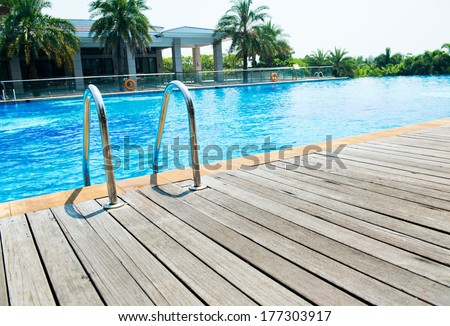 Swimming pool with stair and wooden deck  - stock photo