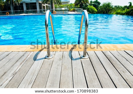 Swimming pool with stair and wooden deck at hotel. - stock photo