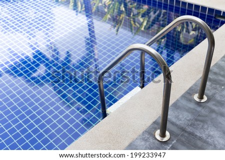 Swimming pool with stair (selective focus) - stock photo