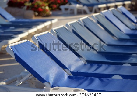 Swimming pool with sun beds at the hotel - stock photo