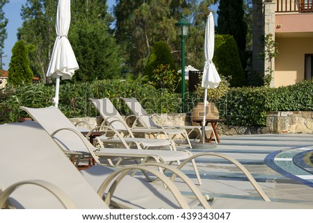 Swimming pool with sunbeds and umbrellas, beautiful swimming pool in tropical resort - stock photo