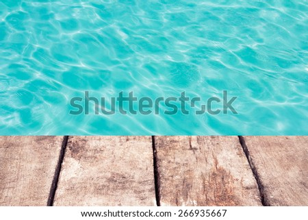 swimming pool with sunny reflections and wood floor background - stock photo