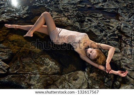 Swimsuit model posing sexy in front of black lava field on at Palos Verdes, CA - stock photo