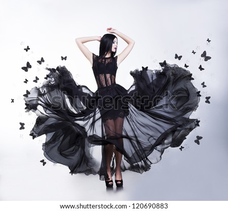 Swing. Flutter. Sensual Woman in Black Evening Fluttering Dress with Butterflies - stock photo