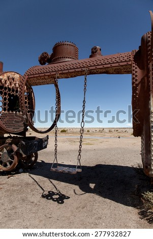 Swing hanging on a old rusty locomotive. Shadow on the ground and blue sky background - stock photo