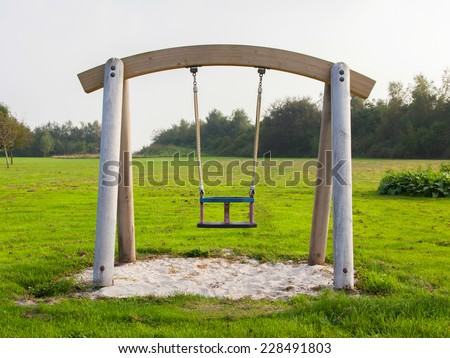 Swing in a park, playground for kids - stock photo