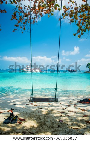 Swing in a perfect beautiful paradise beach with a ship, tourists, and pretty leaves at Koh Chang Island in Thailand - stock photo