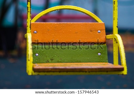 Swinging Rain. Closeup view of a swing on a playground in a rainy autumn day against the blurry background. Everything is wet and water-soaked. The summer season is over. - stock photo