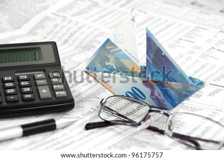 Swiss Banknote is folded as boat on the stock paper with eye-glass and calculator - stock photo