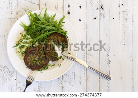 Swiss chard veggie fritters with mash potatoes and rocket leaves on white plate, fork and knife and white rough background, copy splace - stock photo