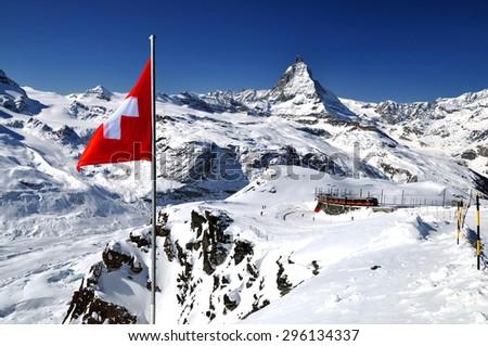 Swiss flag and ski slope in mountains near Zermatt, Switzerland. Swiss Alps with Matterhorn (peak Cervino), swiss flag and train. - stock photo