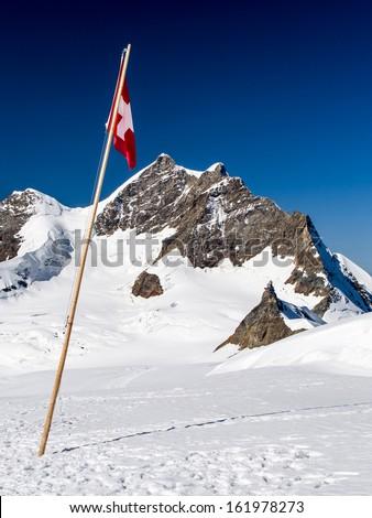 Swiss flag in Jungfraujoch pass in the Alps - stock photo