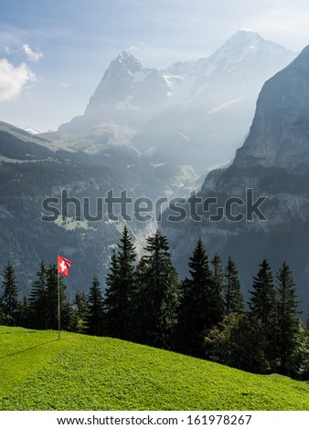 Swiss flag in the mountains on the grass with Eiger mountain at the back - stock photo