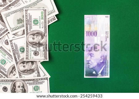 swiss francs and dollars. money from switzerland in europe on green background - stock photo