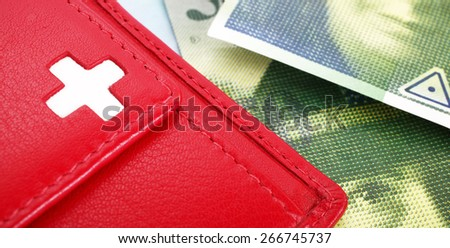 Swiss francs banknotes and red wallet with Swiss flag - stock photo