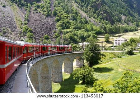 Swiss mountain train Bernina Express  passes the spiral of the Brusio Viaduct - stock photo