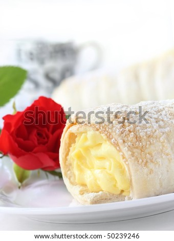 swiss pastry -?? cream cones / cornet with vanilla filling with red rose as deco - stock photo