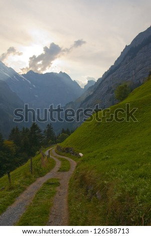 Swiss valley and mountains with cloud blocking bright sunlight - stock photo