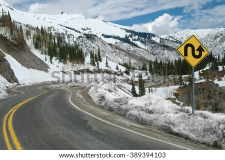Switchback Road and Sign:  A sign warns of repeated sharp turns ahead on a mountain road in southwest Colorado.  - stock photo