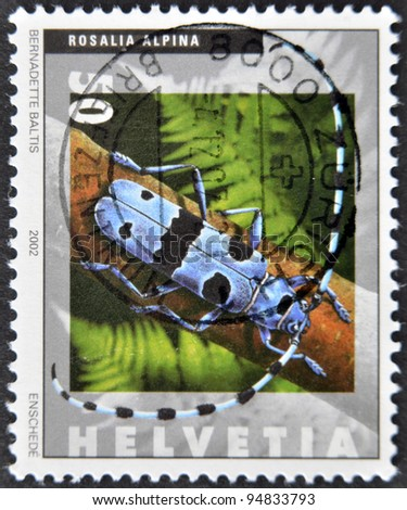 SWITZERLAND - CIRCA 2002: A stamp printed in Switzerland shows rosalia alpina, circa 2002 - stock photo