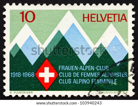 SWITZERLAND - CIRCA 1968: a stamp printed in the Switzerland shows Mountains and Emblem of the Swiss Women�s Alpine Club, 50th Anniversary, circa 1968 - stock photo