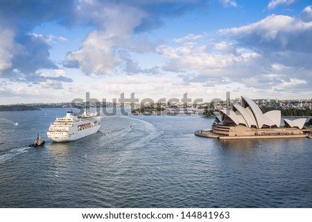 SYDNEY - APRIL 17: The Overseas Cruise Ship sailing past the Sydney Opera House on April 17, 2013 in Sydney, Australia. The ship provides transportation between the Pacific and New Zealand. - stock photo