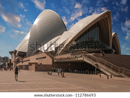 SYDNEY - AUGUST 13: People walks along Sydney Opera House on August 13, 2010 in Sydney. The Landmark is a famous arts center. It was designed by Danish architect Jorn Utzon, finally opening in 1973. - stock photo