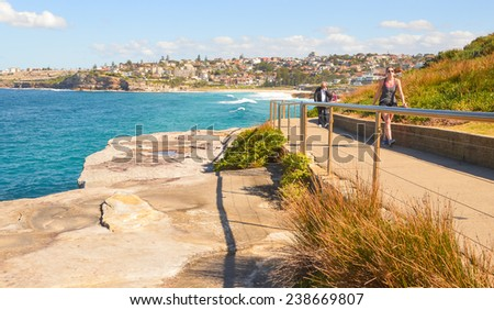 SYDNEY, AUSTRALIA - AUGUST 3 , 2014 : People are walking along the pathway at the seaside of Bondi beach - stock photo