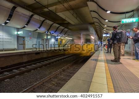 SYDNEY, AUSTRALIA - 31 AUGUST 2013 : Travelers stand on platform in Sydney International Airport train station as the commuter train passes by. Motion blur to denote speed. - stock photo