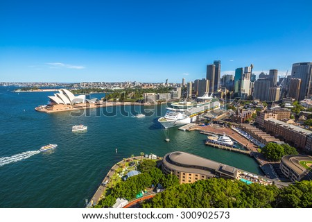 Sydney, Australia - December 29, 2014: skyline scenery with famous Opera House, Royal Botanic Gardens, Circular Quay, harbor with huge transoceanic ship, Sydney Tower, other downtown buildings - stock photo