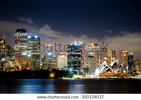 SYDNEY, AUSTRALIA - JANUARY 8, 2014: Sydney Harbour with Sydney Opera House at night. The Sydney Opera House hosts over 1,500 performances each year that are attended by more tnan 1.2 million people. - stock photo