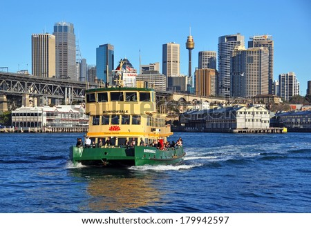 SYDNEY, AUSTRALIA - JULY 03, 2011: One of Sydney's famous green and yellow ferry boats crosses the harbour from Darling Harbour to McMahons Point. In the background is the Sydney city CBD. - stock photo