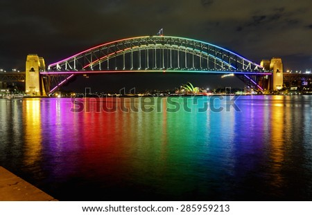 SYDNEY, AUSTRALIA - JUNE 3, 2013;  Sydney Harbour Bridge lit in vibrant rainbow colours and reflections in Sydney Harbour.  Sydney Opera House in far view. - stock photo