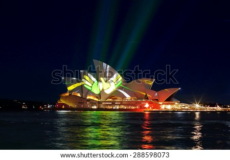 SYDNEY, AUSTRALIA - JUNE 2, 2015; Sydney Opera House illuminated with colourful animated imagery of bright yellow and green hands - stock photo