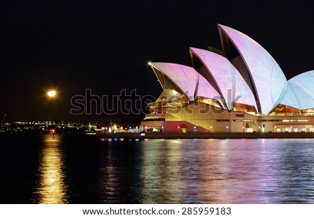 SYDNEY, AUSTRALIA - JUNE 8, 2015;  Sydney Opera House in a myriad of colours and patterns and reflections in the Sydney Harbour waters.  The moon rising in the far east. - stock photo